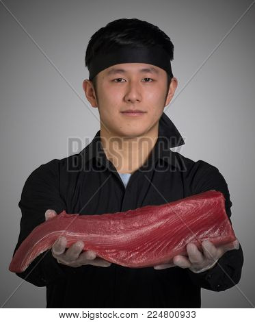 Asian cook hold a tuna fish fillet for sushi food