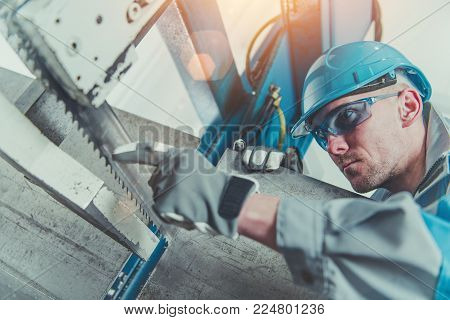 Heavy Duty Metal Cutter Operator. Metalworking Industry Concept. Caucasian Technician Checking on the Process Inside the Cutter.