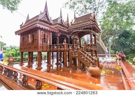 Beautiful Thai style spirit house or house of the guardian spirit is made of wood and sculptured wood. Thai houses ancient style pattern. Foreshorten.