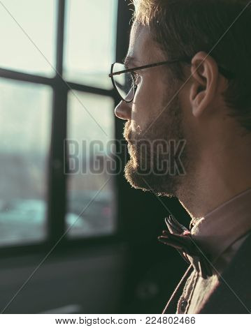 close-up view of bearded young man in eyeglasses and bow tie looking away