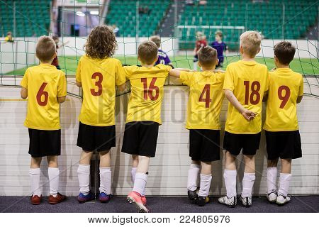 Indoor soccer team. Futsal indoor soccer match for kids. Children supporting teammates. Sports arena in the background. Indoor football school tournament for kids