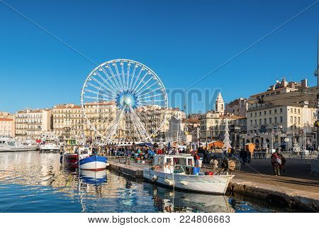 Marseille, France - December 4, 2016: Fish market in Old Vieux Port is the popular tourist attraction in Marseille, Provence, France. Fishing boats in the foreground.