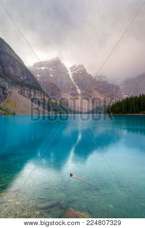 Morning fog and low clouds descend upon the Valley of Ten Peaks surrounding the turquoise-colored Moraine Lake at Lake Louise in Alberta, Canada, near Banff National Park. Vertical orientation.
