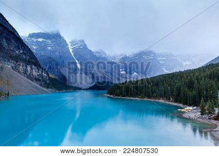 Early morning fog and low clouds descend upon the Valley of Ten Peaks surrounding the turquoise-colored Moraine Lake at Lake Louise in Alberta, Canada, near Banff National Park.