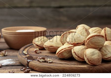 homemade cookies shaped nuts with cream boiled condensed milk on wooden table. Rustic style. condensed milk drains from a cutting board