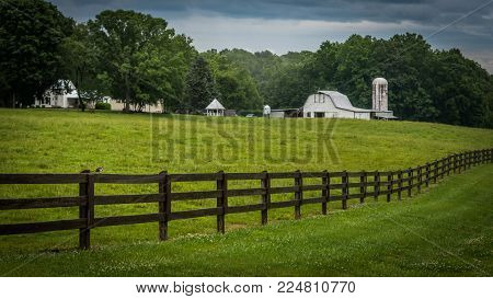 A pasture with a fence and farm, farm house and trees in the background