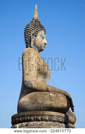 Ancient sculpture of a seated Buddha close-up against a blue sky. Sukhothai, Thailand