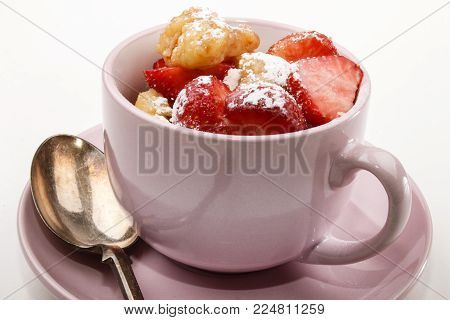 homemade kaiserschmarrn with strawberries and icing sugar in a pink cup