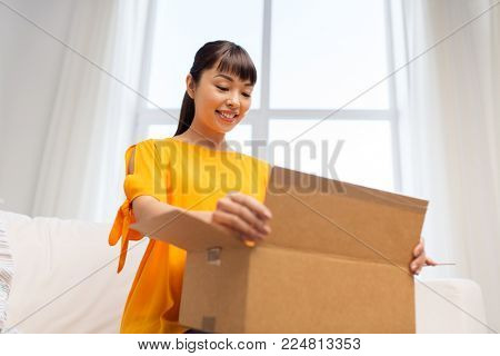 people, delivery and shipping concept - happy asian young woman with parcel box at home
