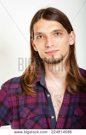 Masculinity concept. Smiling guy with long hairs. Young man in plaid shirt.