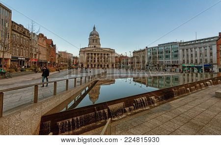 Nottingham, England - February 02, 2018: Various people sitting, walking, visiting in the main Market Square, Nottingham Council House building behind.