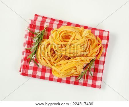 bundles of dried ribbon pasta on checkered place mat