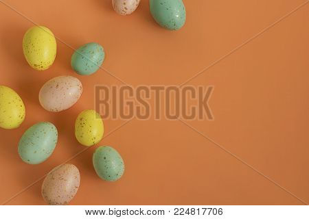 Gold speckled Easter eggs on a bright orange background.