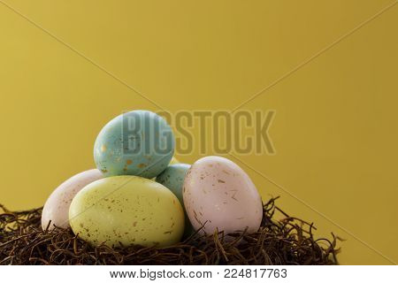 Gold speckled Easter eggs on a nest against a bright yellow background.