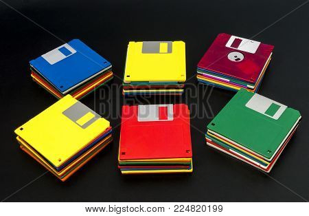 Horizontal shot of six stacks of multicolored plastic disks on a black background.  Some of the stacks are angled out.  The middle two stacks are straight.