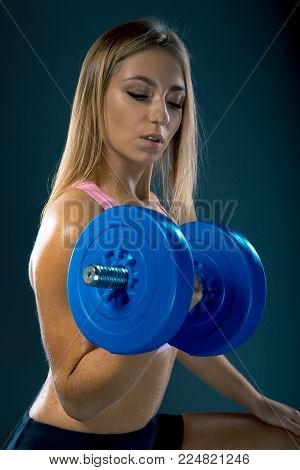 Nice sexy blonde woman doing workout with dumbbells over dark background