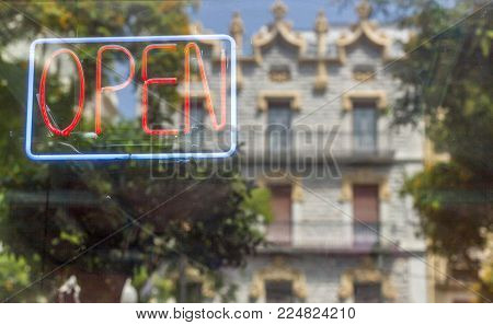 Sign Open neon with artistic facade building reflection.