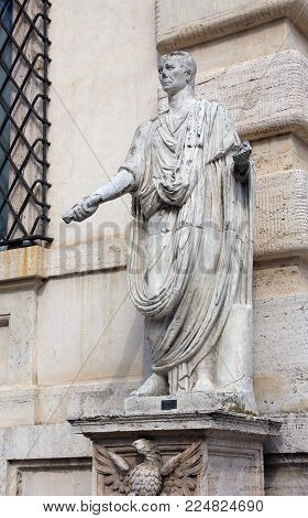 antique white marble statue of Roman patrician in toga with sumdam in hand on street of Rome in Italy