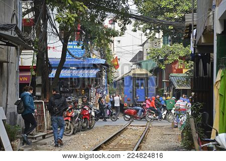 Hanoi, Vietnam - 16th December 2017. The 15.30 train from Hanoi to Sapa as it goes along a narrow residential street in central Hanoi which has grown up around the north-bound train track. The street is often referred to as train street