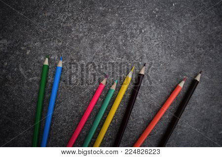 Eight color pencils on grey background. Colored drawing pencils. A variety of colors of drawing pencils.