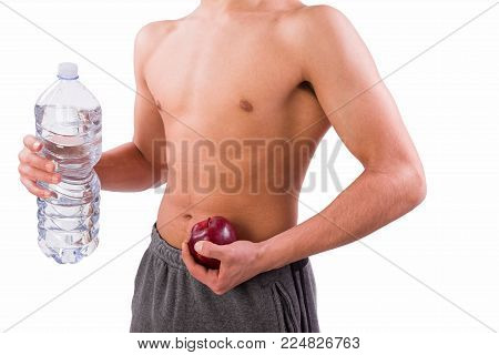 Young sporty man holding red apple and bottle of water. Sport or healthy life concept. White background with copy space.