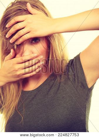 Emotions, embarrassment, awkwardness gestures concept. Ashamed blonde woman covering her face with hands. Studio shot on white background.