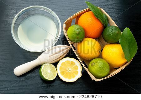 Healthy Food And Vitamins: A Wooden Juicer And Green Fresh Lime With Juice On A Black Table