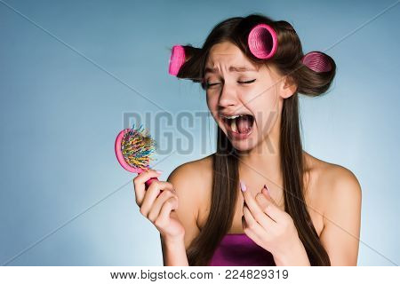 frustrated with hair loss woman with hair curlers on her head