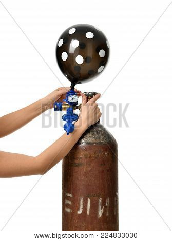 Hands inflate black dotted balloon use Helium Tank with Economy Regulator Fill Valve for Latex Balloons isolated on white background