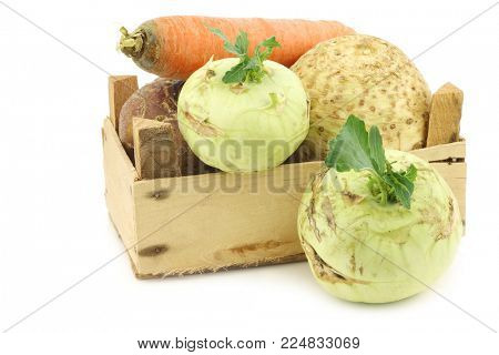 mixed cabbage and root vegetables in a wooden crate on a white background