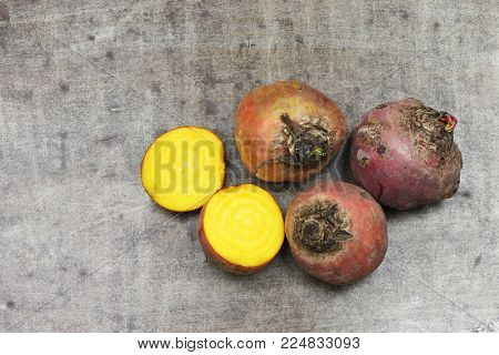 freshly harvested yellow beets and two halves on a grungy metal background