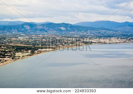 The entrance to the Corinth Canal from Ionian Sea and the Corinthian cityscape.
