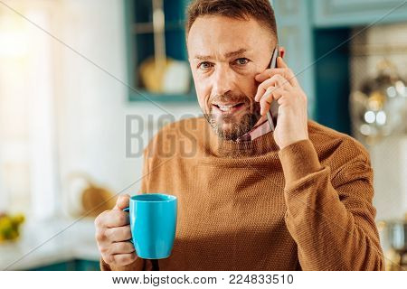 Distance communication. Positive joyful bearded man holding a cup of tea and looking at you while making a phone call