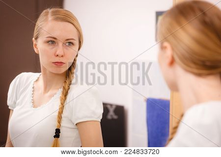 Woman looking at her reflection in mirror thinking about her complexes having serious face expression, analyzing face skin complexion.