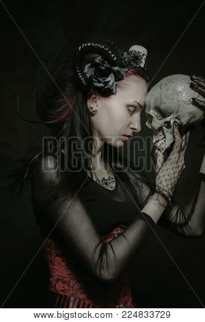 Young horned beautiful lady posing over dark background with skull