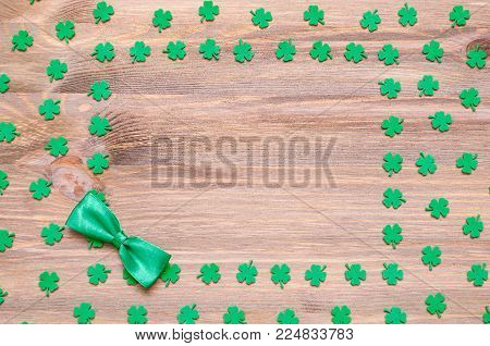 St Patrick's Day festive background, green quatrefoils and bow tie on the wooden background with free space for St Patrick's day text