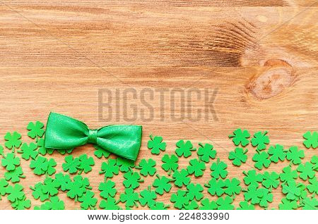 St Patricks Day background - bright green quatrefoils and bow tie on the wooden background,with copy space for St Patricks Day text. Colorful St Patricks Day border background