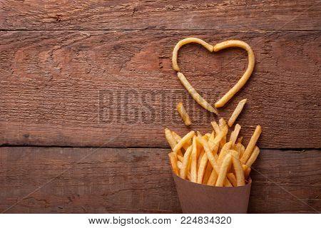 I love fried potatoes. French fries in a paper box and symbol of a heart on a wooden table