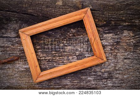 Wooden frame on old wood table background.