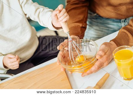Omelet preparation. Close up of a bowl with eggs being in hands of positive happy delighted father and son while preparing an omelet