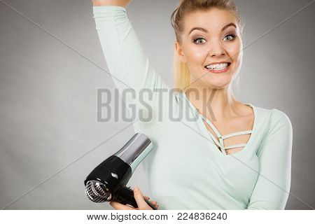 Woman drying wet armpit using hair dryer. Getting rid of sweat and bad smell, hyperhidrosis. poster