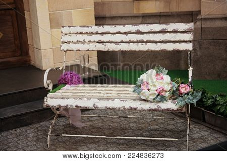 White bench in front of a house. Bouquet flowers on a bench