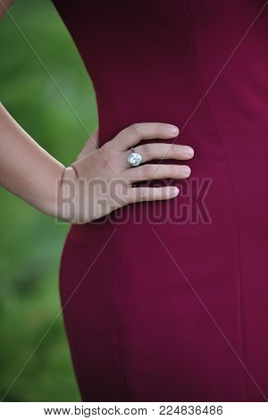 Beautiful girl with hand on hip in park. Ring on the right hand