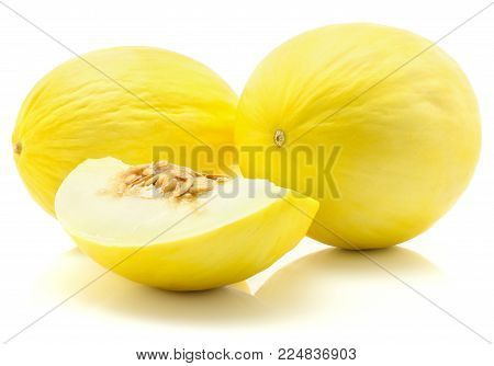 Two yellow honeydew melons with a fleshy slice isolated on white background