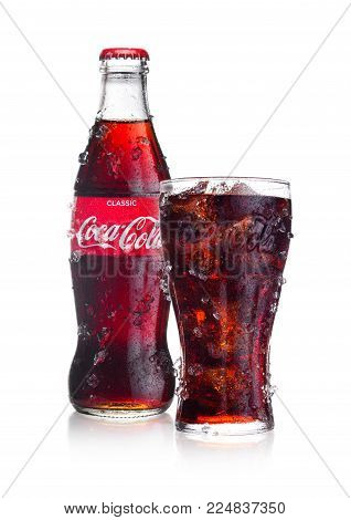 LONDON, UK - FEBRUARY 02, 2018: Cold bottle and glass of Classic Coca Cola  drink on white background with ice and dew. The drink is produced and manufactured by The Coca-Cola Company.
