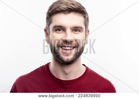 Attractive male. Close up of a handsome upbeat young man in a burgundy t-shirt smiling at the camera while posing isolated on a white background