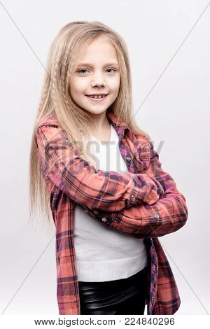 Wannabe model. The studio shot of a beautiful fair-haired little girl in a checked shirt on top of a white t-shirt folding her arms across her chest and posing