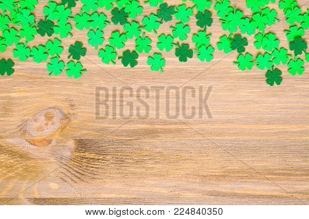St Patrick's Day background, one side border with green quatrefoils on the wooden background and free space for St Patrick's day festive text. Colorful St Patrick's day card
