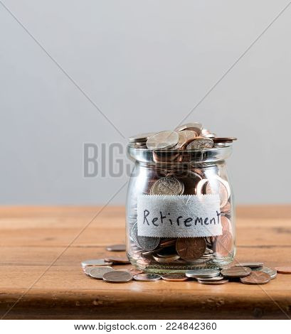 Glass savings jar full of loose change and coins to illustrate investment planning for retirement