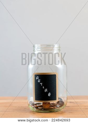 Loose change and coins inside a glass jar against a grey background to represent lack of retirement savings